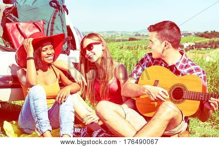 Friends summer camp with guitar and car on countryside background - Multiracial teens having fun with music relax on grass field outdoors