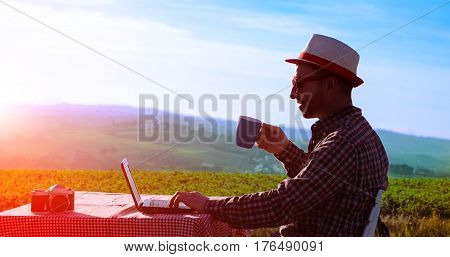 Man drinking coffee and working at laptop at sunset on countryside background surrounding - Silhouette of middle aged happy farmer relaxing with cup and pc at dusk light