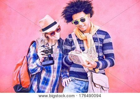 Interracial couple of tourists holding camera and looking tour guide - Attractive latinos traveler leaning at colorful city wall pointing map book smiling in happy attitude