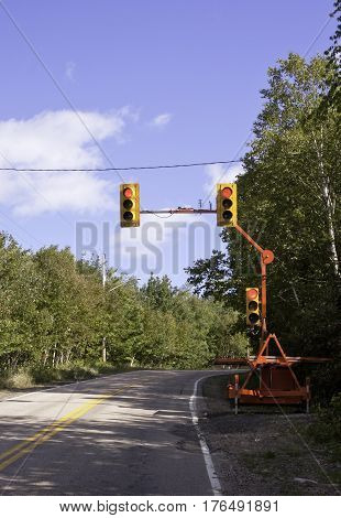 Vertical of a mobile set of traffic lights is parked beside a rural highway in Cape Breton, Nova Scotia on a beautiful bright sunny day in September.
