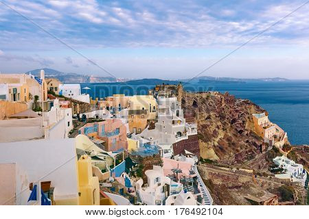 Picturesque panorama of Oia or Ia on the island Santorini, white houses, windmills and church with blue domes, Greece