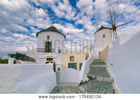 Picturesque white houses and windmills in Oia or Ia on the island Santorini, Greece