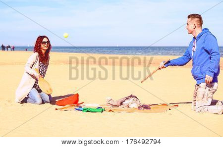 Couple playing beach tennis game on the sand with blue ocean and sky background - Playful young family having fun at weekend on sunny spring day - Concept of joyful moment and active lifestyle