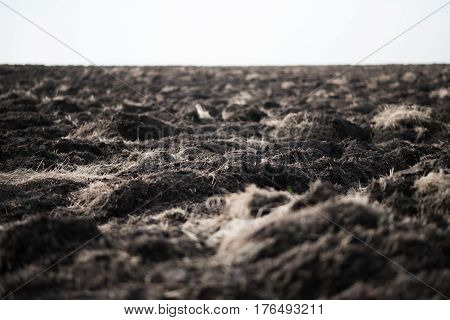 Plowed agriculture field. The furrows in the soil. Early spring in March.