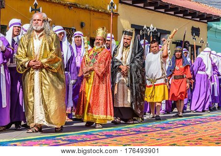 Antigua, Guatemala - March 25 2016: Locals reenact biblical scenes walking over handmade dyed sawdust carpets on Good Friday in colonial town with most famous Holy Week celebrations in Latin America.