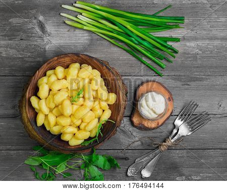 Homemade Potato dumplings Gnocchi in wooden plate. On gray wooden table background ingredients for Potato dumplings Gnocchi Salad of rucola fresh green onion sauce forks.