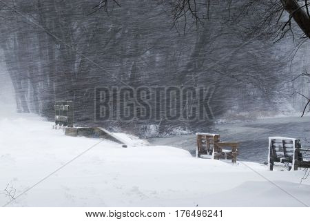 Snow blowing sideways over a pond and a bridge with a park bench on the side.