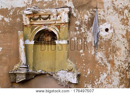 Wall of abandoned ruined building with niche for sculpture