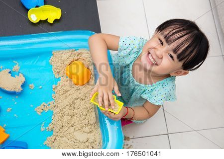 Happy Asian Chinese Little Girl Playing Kinetic Sand At Home