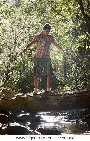 Teenage boy (16-17 years) walking tree trunk above stream