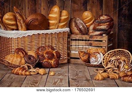 Composition with bread and rolls in wicker basket. Isolated over dark background