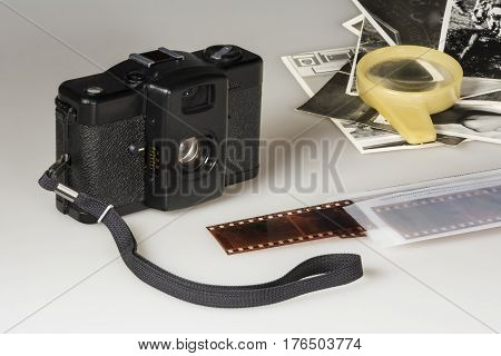 Old compact camera negatives black-and-white photos and a magnifying glass on a table on a white background
