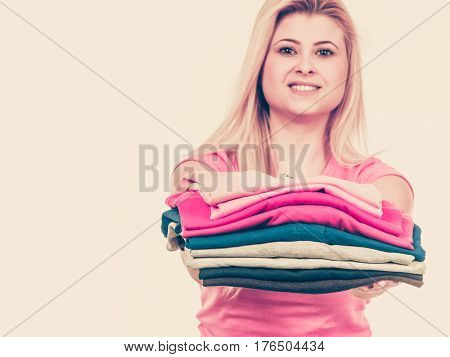 Woman Holding Pile Of Folded Clothes