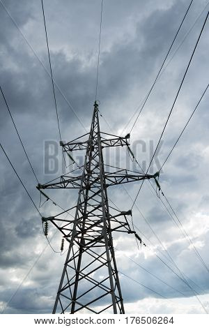 High voltage electricity pylon against thundercloud. Electric pole power lines and wires.