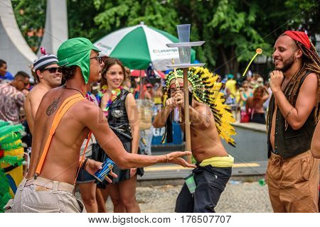 RIO DE JANEIRO, BRAZIL - FEBRUARY 28, 2017: Man in a costume of Indigenous people, wearing a crown of feathers, shooting a bow and arrow with suction cup in target made of plastic cups, Carnaval 2017