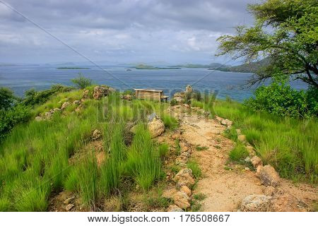 Hiking trail and a bench at the viewpoint on Kanawa Island in Flores Sea Nusa Tenggara Indonesia. Kanawa Island is within the Komodo National Park. poster