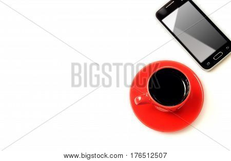 Cup of coffee and cell phone and white background on top. Isolated objects on a white background with a shadow. Horizontal format. Indoors. Color. Photo. Without people.