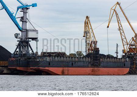 Black barge loading in cargo port of Riga