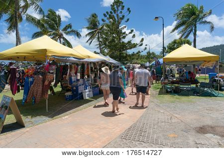 Airlie Beach, Australia - February 04, 2017: Saturday farmers market at Airlie beach with people stralling along vendor stalls and palm trees on the background
