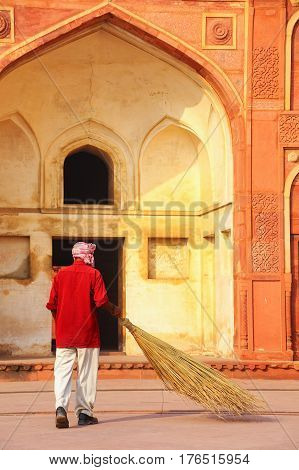 Local worker sweeping courtyard of Jahangiri Mahal in Agra Fort Uttar Pradesh India. The fort was built primarily as a military structure but was later upgraded to a palace.