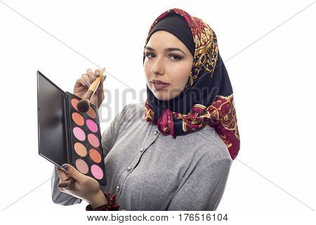 Female make up artist wearing a red hijab with a cosmetic palette to depict conservative fashion. The headscarf is associated with muslims and middle eastern culture.