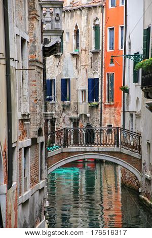Houses Along Narrow Canal Connected By A Stone Bridge In Venice, Italy