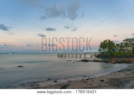 Pier, jetty, berth in tropical surroundings against sunset sky on the background