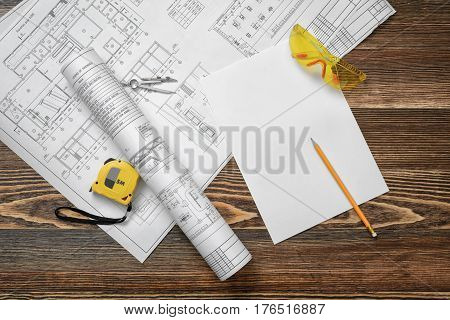 Blueprints, pencil, protective glasses, steel tape, pencil and white paper lying on wooden table background. Construction and renovation. Workers and foremen. Engineering supplies.