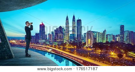 Business Man use the telescope to watch the modern city skyline is about looking forward for search key success business concept .