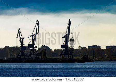 Cargo cranes silhouette in the morning Riga