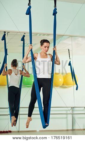 Young attractive yogi woman doing aerial yoga