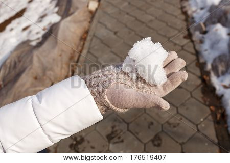 Hands of the person hold the thawing snow in hand in the winter