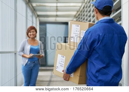 Postman carrying cardboard boxes to happy woman