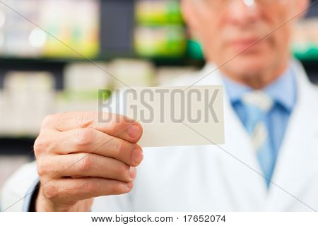 Pharmacist with business card in pharmacy; focus on card