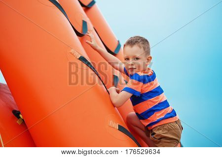 Boy Playing On An Inflatable Playground On The Beach On A Summer Day.