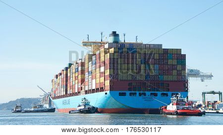 Oakland CA - March 14 2017: Cargo ship CRETE MAERSK with multiple tugboats assisting the vessel to maneuver to the dock at the Port of Oakland.