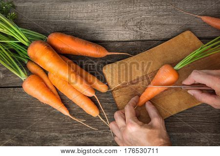 Female cuts fresh organic carrots with green tops on wooden table. Copy space. Top view.