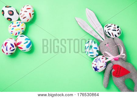 Easter eggs in a paper bag. Green background. Easter bunny. Rabbit. Easter ideas. Space for text. Black lettering on a heart happy easter.