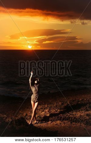 Pretty Girl On Rocky Shore At Sea During Idyllic Sunset