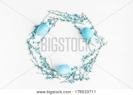 Blue easter eggs and flowers on white background. Easter concept. Flat lay top view