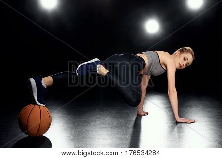 Attractive Sportswoman In Plank Position With Basketball Ball On Black