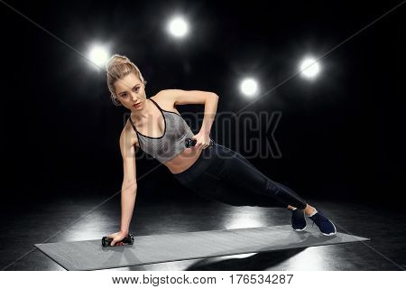 Attractive Sportswoman In Side Plank Position With Dumbbells On Black