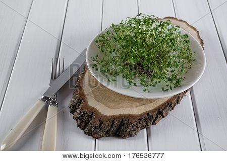 Garden cress on white plate with fork and knife. Healthy vegetarian food. Fresh herbs.