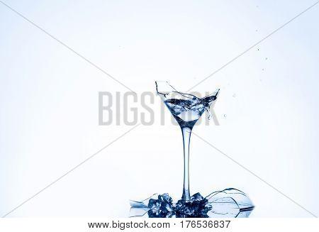 Water splash in a broken goblet. Water drops in a glass. Shattered goblet