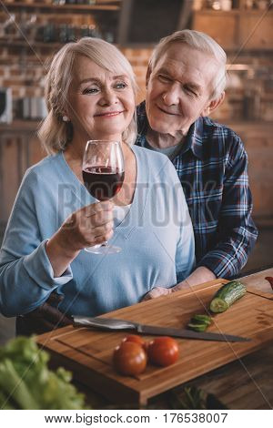Happy Senior Couple Drinking Wine And Cooking Together