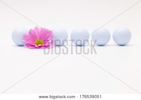 White golf balls and sping flower on the white table