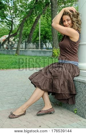 Portrait of beautiful young brunette woman wearing brown dress at summer green park.