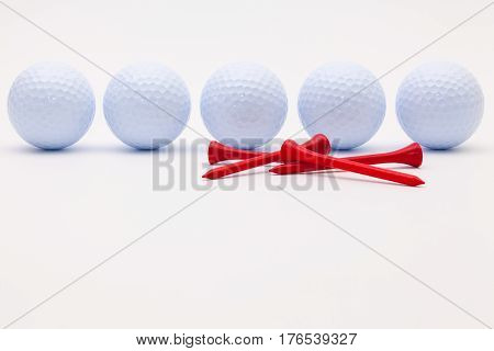 White golf balls and wooden tees on the white background.Golf concept.