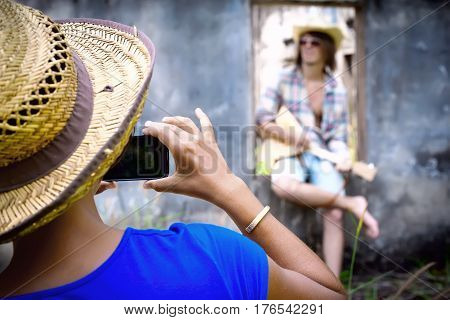 Woman Making Photo Of Man Playing Music With Balalaika