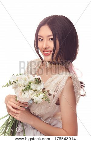 Bride. Woman in the lacy white dress with flowers peonies in hands on a light background. Asian female model posing in studio with bouquet of spring flowers.
